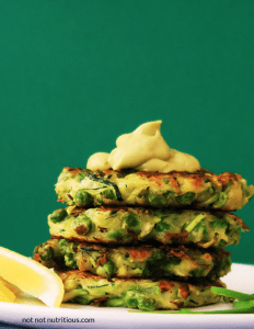 Stack of zucchini and green pea fritters against a green background. The vegan version of this recipe uses aquafaba to replace eggs.