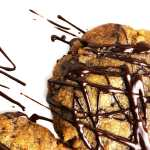 Close up, top-down shot of vegan brown butter chocolate chip cookies, drizzled with dark chocolate, on a white plate