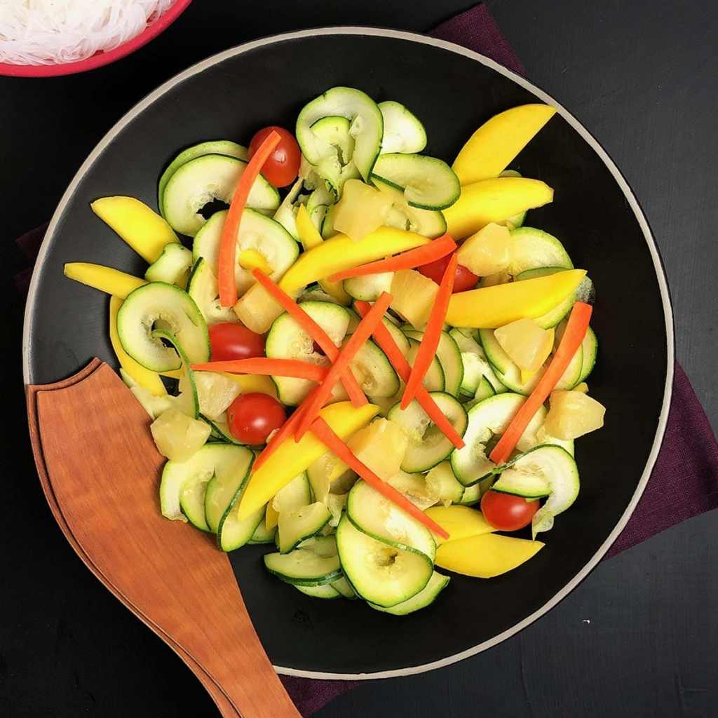 Top down view of black bowl containing mango, pineapple, zucchini, and carrots for Buddha Bowls with Pineapple Brown Butter Teriyaki Sauce