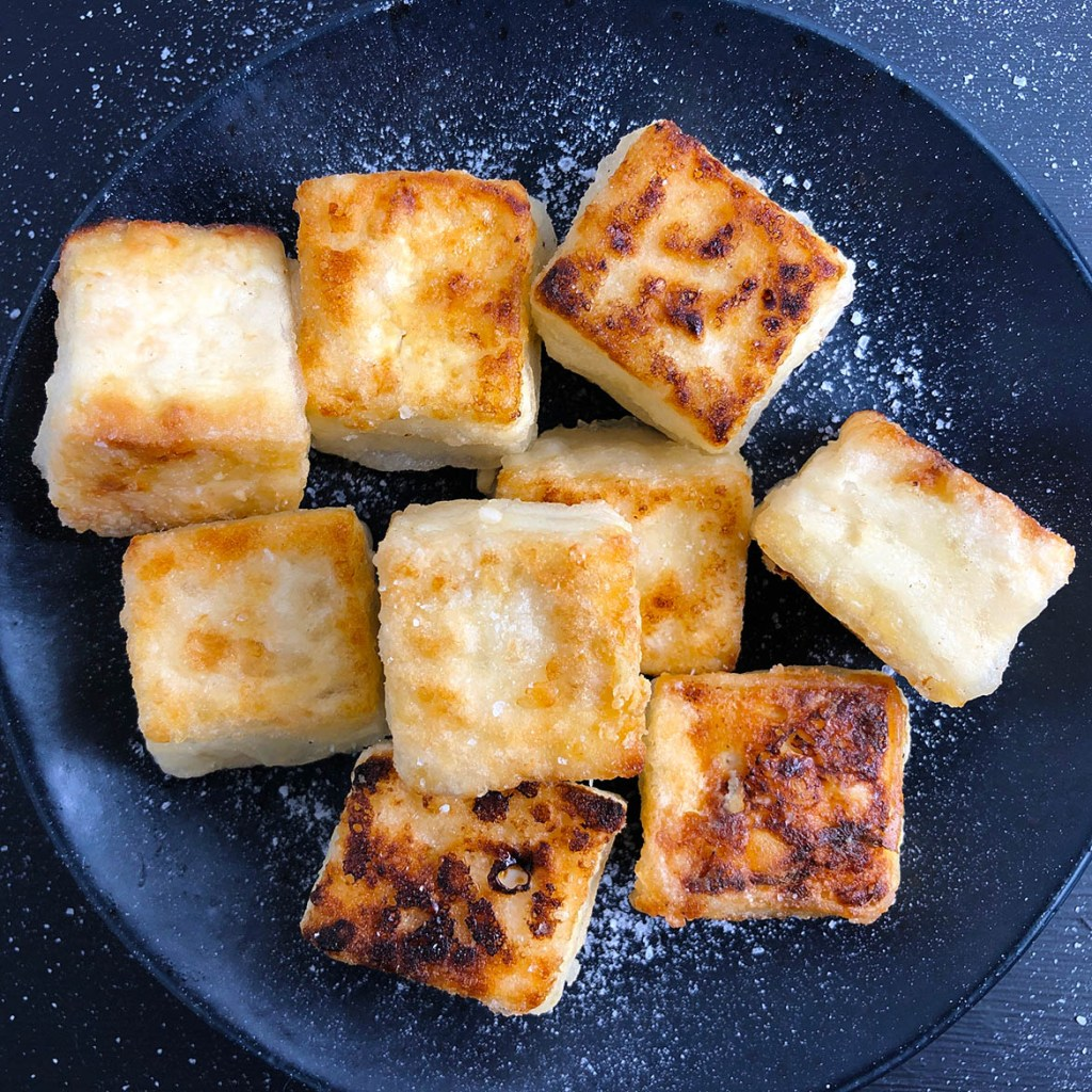 Cubes of Salty Crispy Tofu, sprinkled with salt, on a black plate, all against a black background