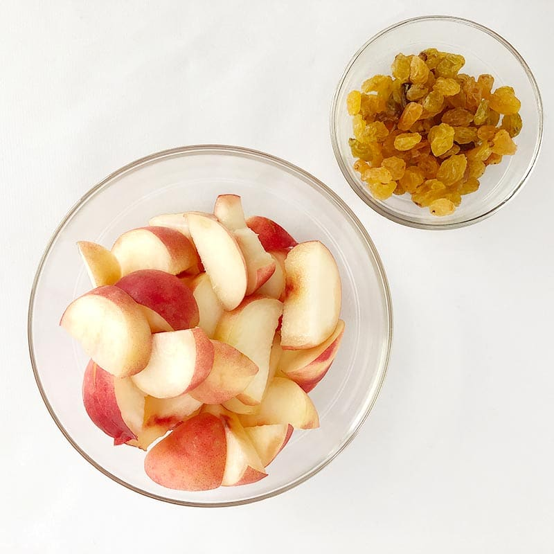 Top-down view of sliced donut peaches in a clear bowl, and a smaller bowl of golden raisins.