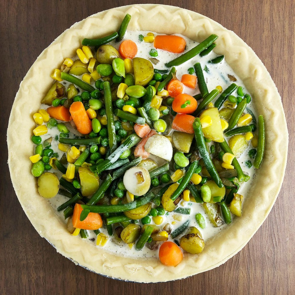 Top-down view of mixed vegetables and Mother Mix sauce in pie shell. Step 4 for making Veggie Pot Pie.