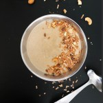 Top-down shot of silver bowl with Indian-Inspired Cashew Sauce against a black background.