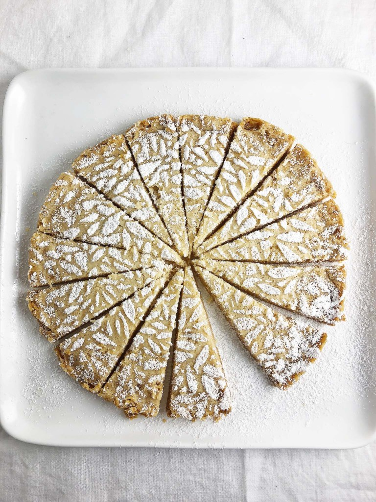 Top-down shot of triangles of Vegan Brown Butter Shortbread on a white plate. Shortbread is decorated with lemon-infused sugar.
