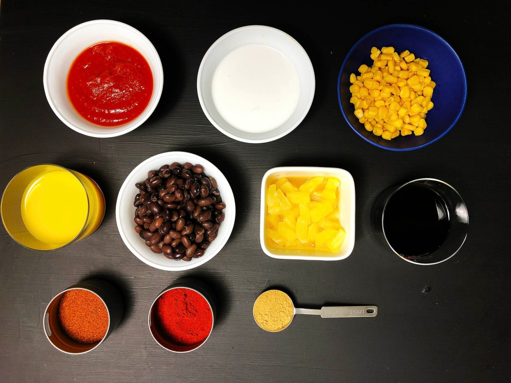 Top-down shot of the ingredients for 1-pot Spicy Black Bean Soup: crushed tomatoes, coconut milk, corn, soya or tamari sauce, pineapples, black beans, orange juice, chili powder, hot chili powder, and ginger powder