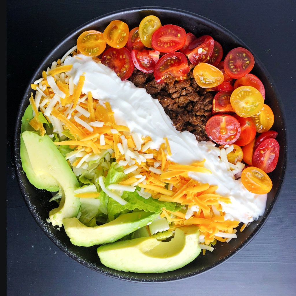Top-down photo of black bowl with taco salad ingredients, shredded lettuce, avocado, shredded cheeses, sour cream, taco meat, and tomatoe
