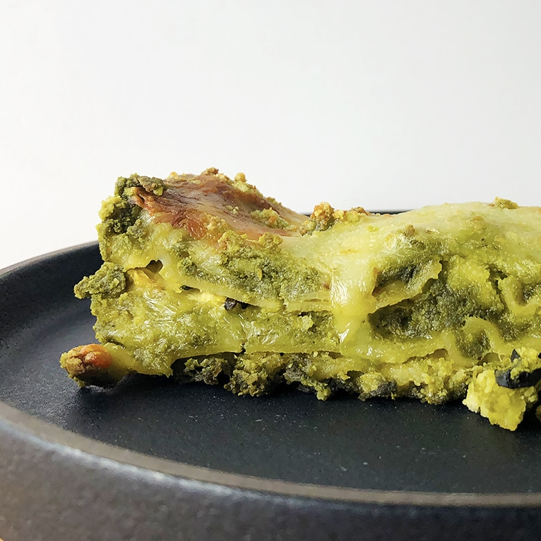 Side shot of slice of Green Lasagna on a black plate against a white background.