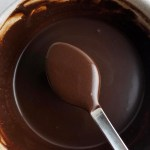 Close-up view of brown butter chocolate sauce pooling over a spoon, over a bowl of chocolate sauce