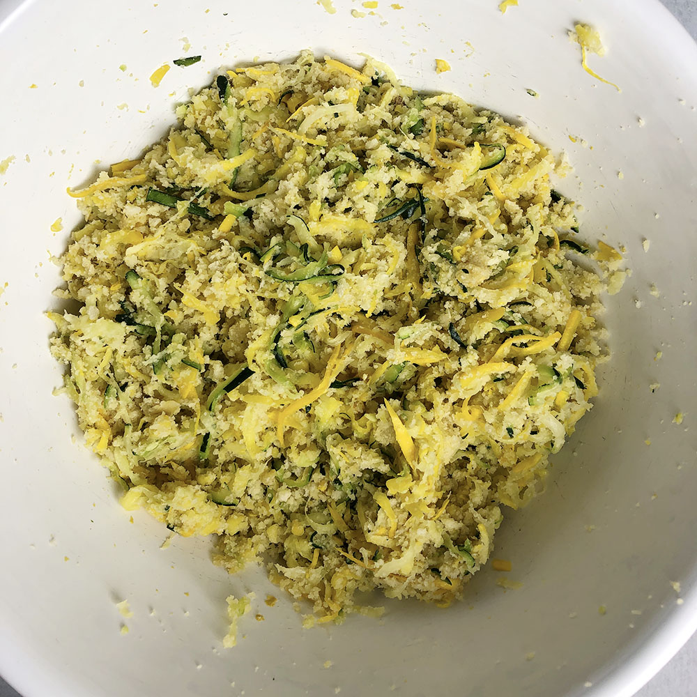 Top-down view of white bowl with zucchini fritter batter, consisting of zucchini, Mother Mix, breadcrumbs, grated lemon rind, garlic, and melted butter or margarine.