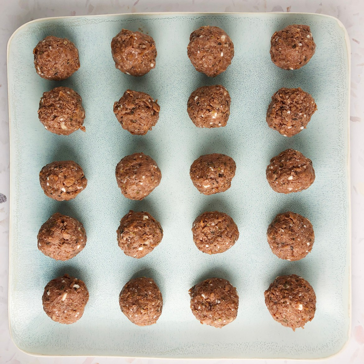 Top-down shot of 20 uncooked mini-meatballs made from Beyond Meat, lined up in rows on a light blue plate.