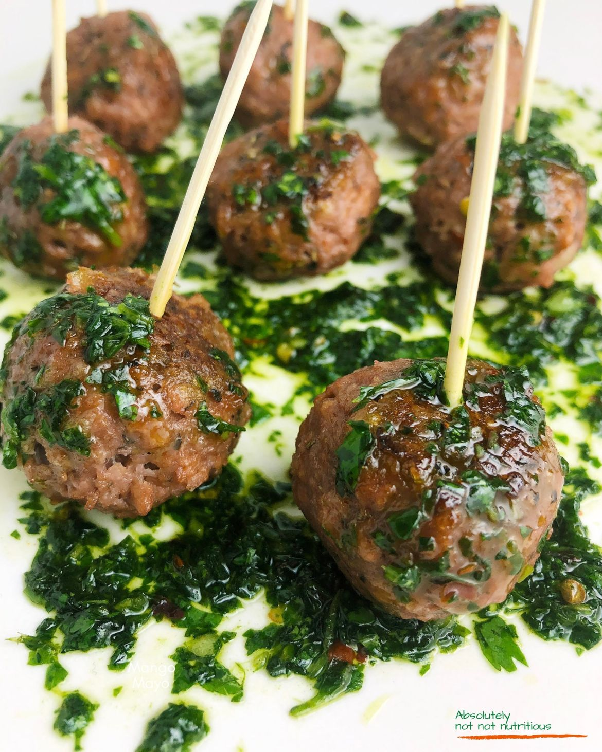 Close-up shot of mini-meatballs made with Beyond Meat plant-based ground. Meatballs are brushed with garlicky chimichurri and are ready for serving with toothpicks in them.