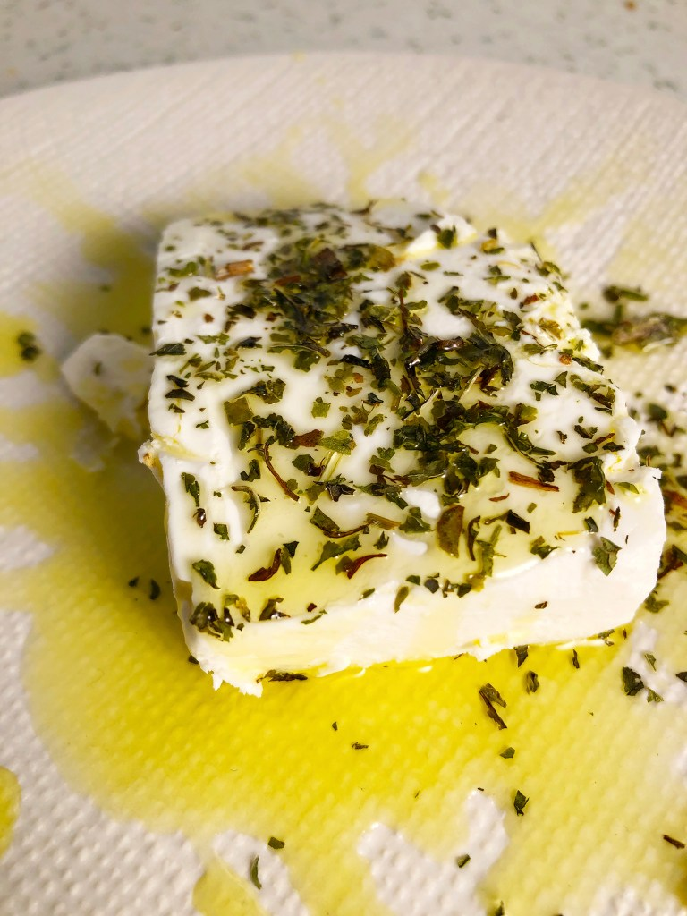 Close up view of a block of Macedonian feta cheese on a textured white plate. Cheese is topped with dried mint and lots of olive oil.