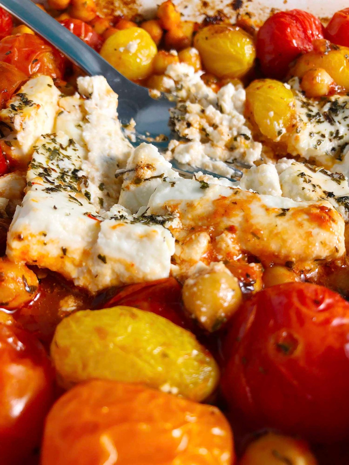 Close up of Chickpea Feta Bake, with fork mashing the baked feta cheese, surrounded by roasted cherry tomatoes and chickpeas.
