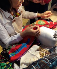 Hand stitching the rolled hem on a scarf, it usually takes 45 minutes per scarf (but not with our interruptions)