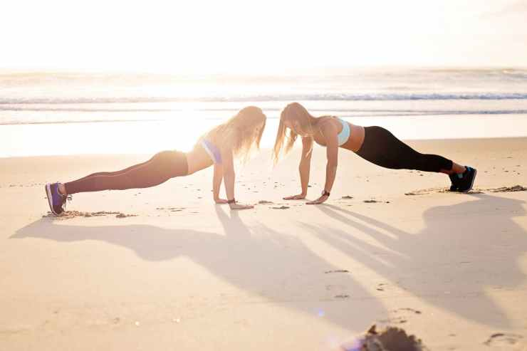two women planking at the seashore