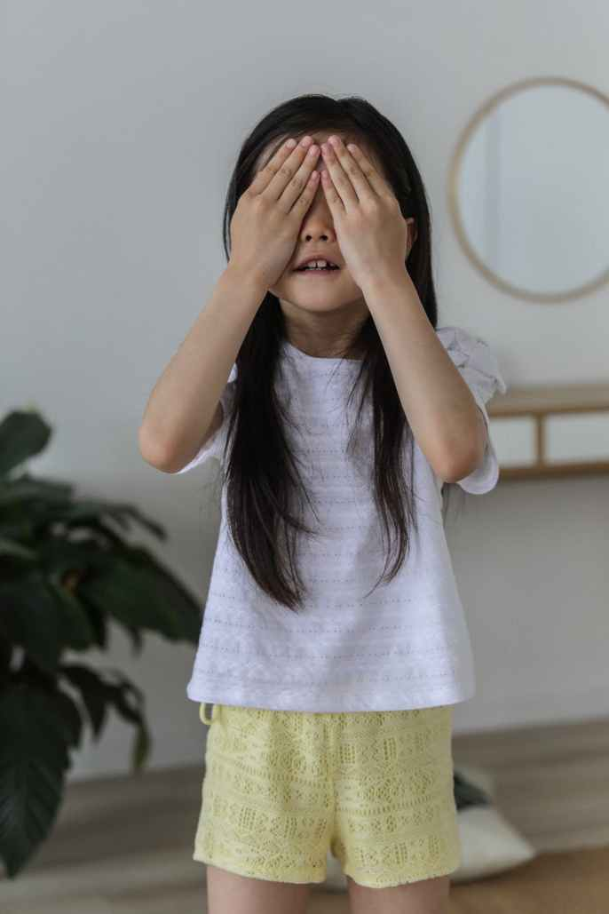 cute asian child hiding face with hands