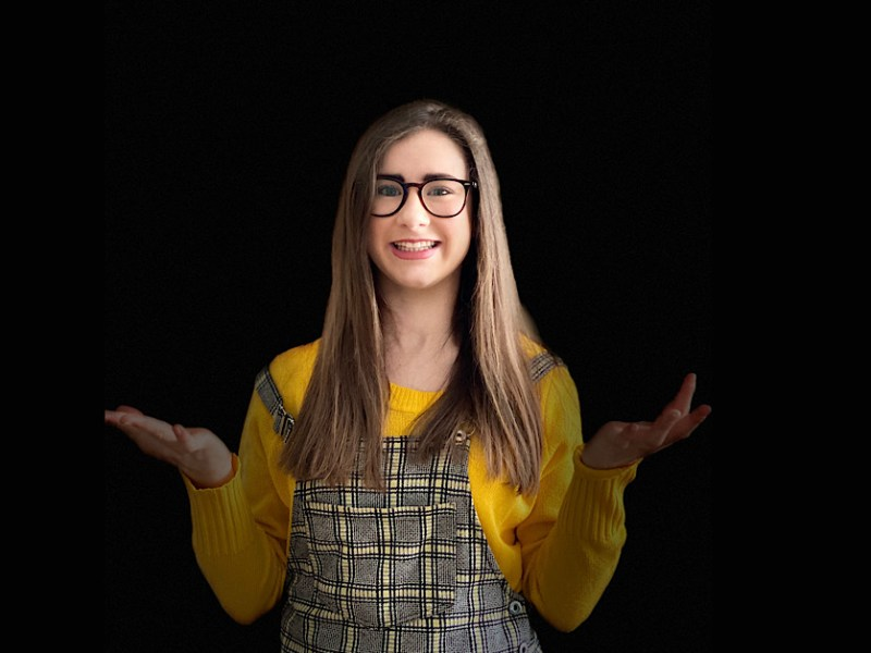 Myself in a yellow jumper and a yellow checked dungaree dress. The background is all black and I am holding my hands up to represent confusion. I have glassed on, minimal makeup and my hair is straight.