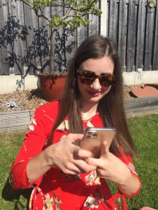 A picture of myself sat on the garden on my phone iPhone 11 Pro Max in a red dress with flowers. It is sunny I have my sunglasses on and a fence is behind me.