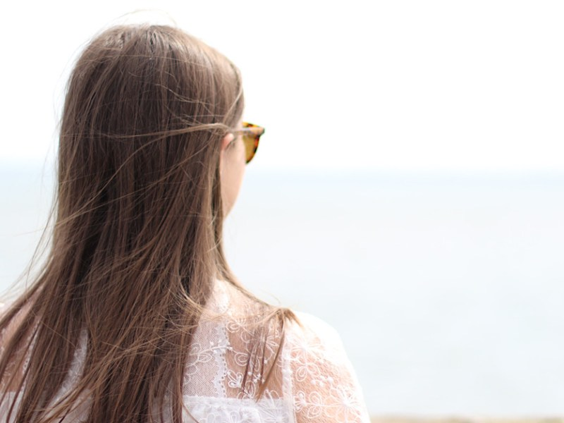 A picture took at the back of me, my hair is straight and you can just see the right side of my sunglasses. I am looking out into the sea but this is very faint. I have a white blouse on with a very intricate patterns of flowers.