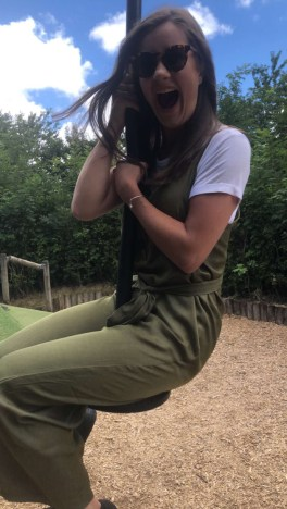 Myself wearing a green jumpsuit with a white t-shirt underneath. I'm wearing sunglasses and I am sat on a zip wire with my mouth open in excitement.