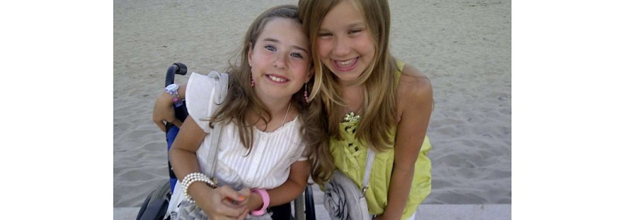 Myself an Matilda aged 10 and 11 I am in a white dress with brown hair in my wheelchair to the left and Matilda in bending down to my height on the right with blonder hair a grey bag and lime green top.