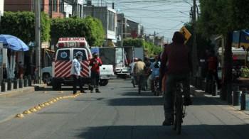 Protección Civil de Cuerámaro, revisando automovilistas, pero a su costado, personas sentadas en el jardín principal.