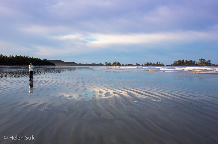 woman strolls across an isolated beach in tofino bc canada