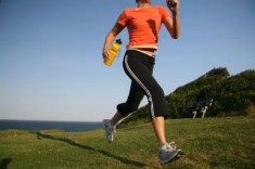 woman running in orange top and black leggings