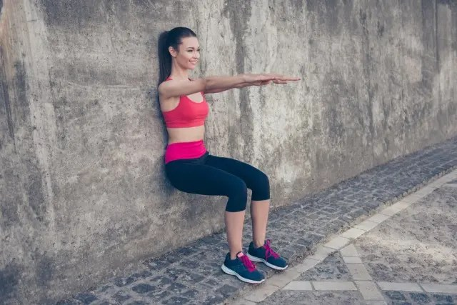 girl in the wall sit test position wearing bright gym kit
