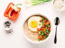 savoury oatmeal idea with tomato, egg and spring onions served in a white bowl