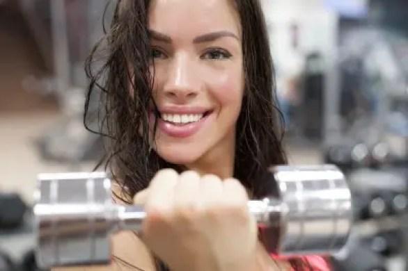 Smiling girl holding a dumbell