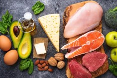 Display of keto-friendly foods including salmon, avocado, steak and eggs