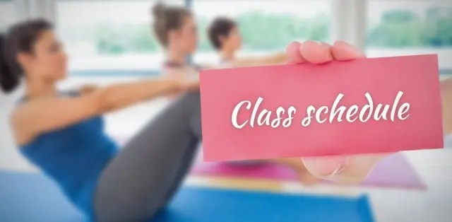 Girl in pilates class holding up a Class Schedule sign