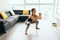 Woman doing squats in her lounge