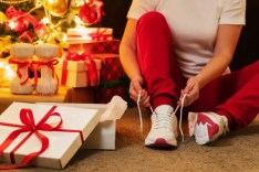 picture of woman lacing up runing shoes surrounded by christmas gifts