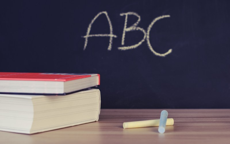 chalkboard with ABC written, chalk on a table next to a pile of books