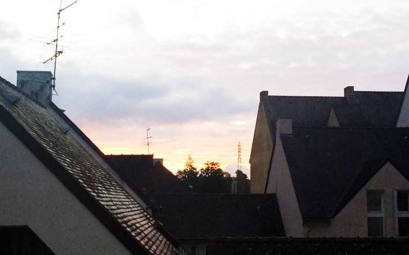 the view of a sunset over rooftops in Lanester, France