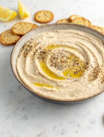 Serving bowl filled with smooth, creamy homemade hummus, garnished with olive oil and sesame seeds, surrounded by crackers.