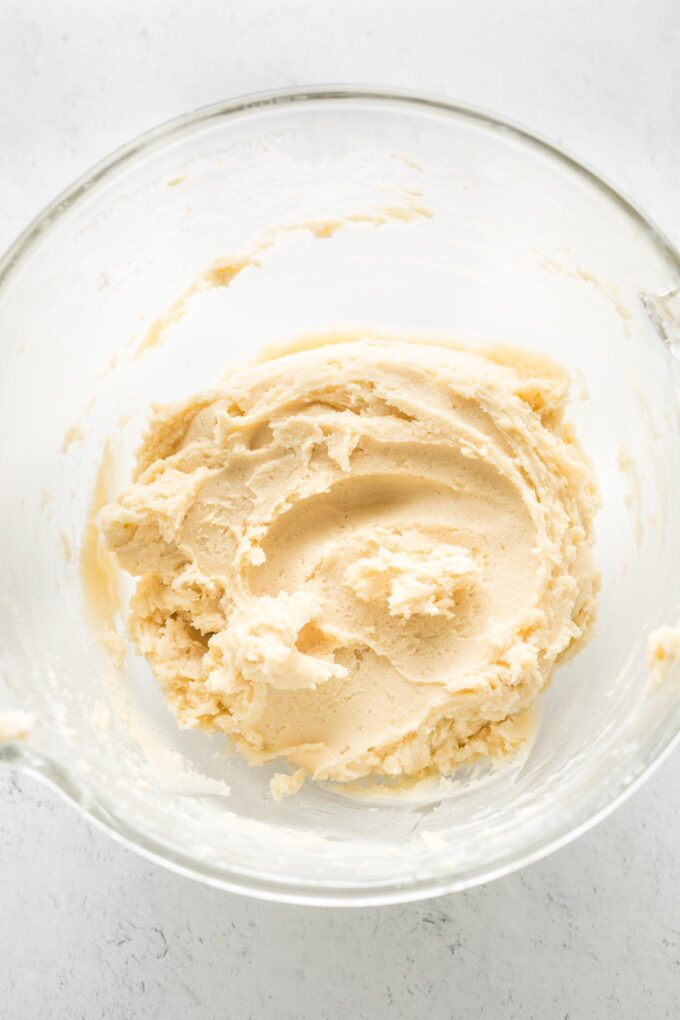 Close-up of soft sugar cookie dough in a clear glass bowl.