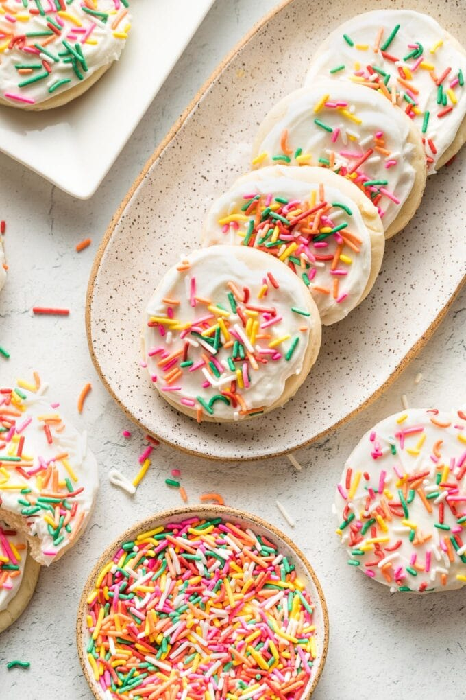 Small plate of soft frosted sugar cookies with multi-colored sprinkles.