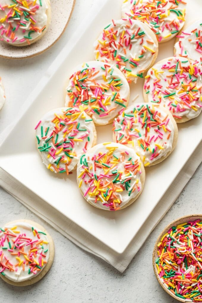 White plate filled with soft frosted sugar cookies, ready to share.
