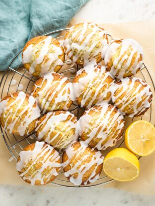 Glazed lemon poppy seed muffins on a cooling rack.