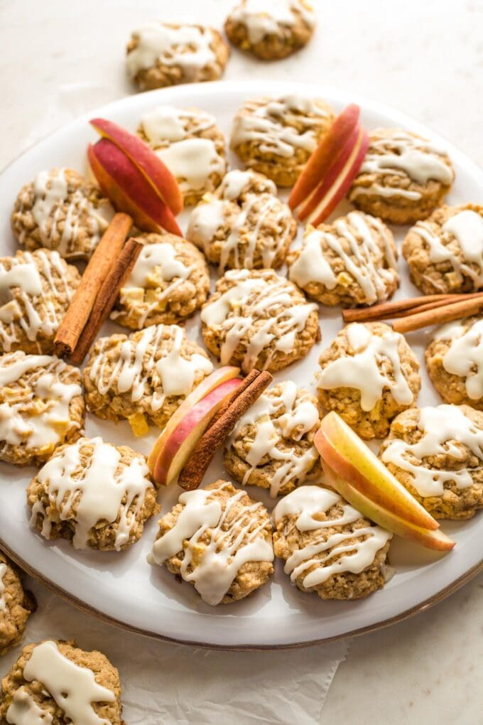 Apple cinnamon oatmeal cookies, arranged on a tray with apple slices and cinnamon sticks for garnish.