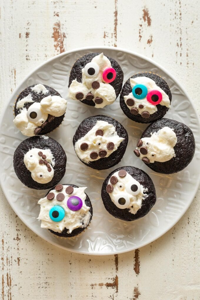 Plate of chocolate cupcakes with messy white frosting and decorations.