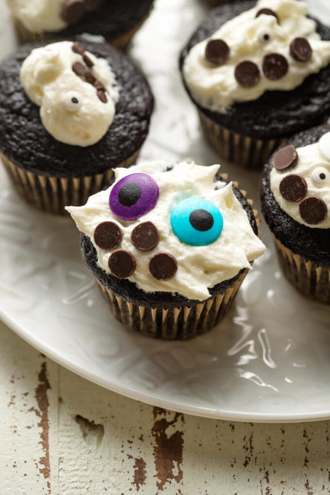 Chocolate cupcake with messy white frosting and colorful decorations.