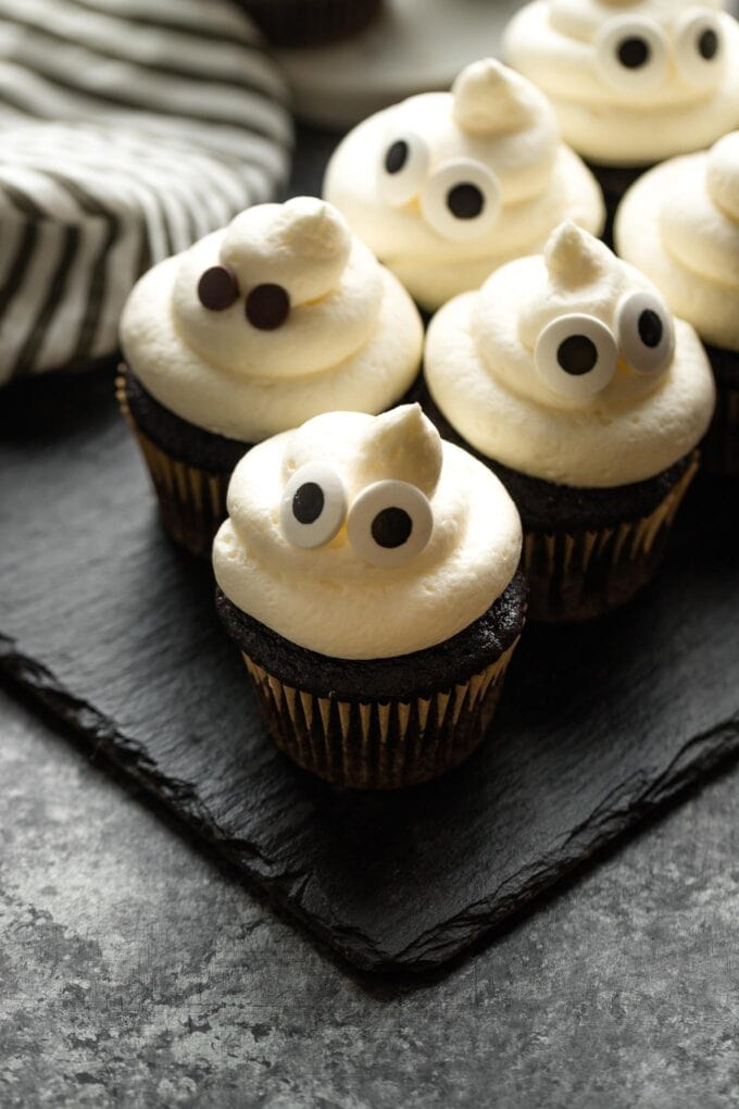 Ghost cupcakes arranged on a slate board.
