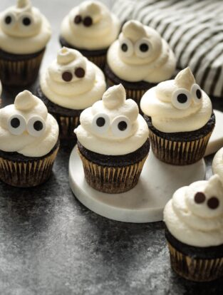 Ghost cupcakes arranged on a black background.