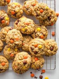 Monster cookies with Reese's pieces on a cooling rack.