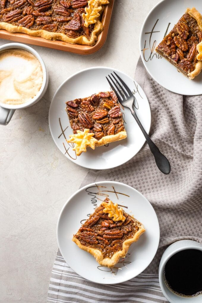 Scene of multiple plates with slab pecan pie served with coffee.