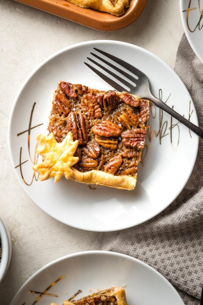 Close-up of a slice of slab pecan pie on a white plate with a fork.